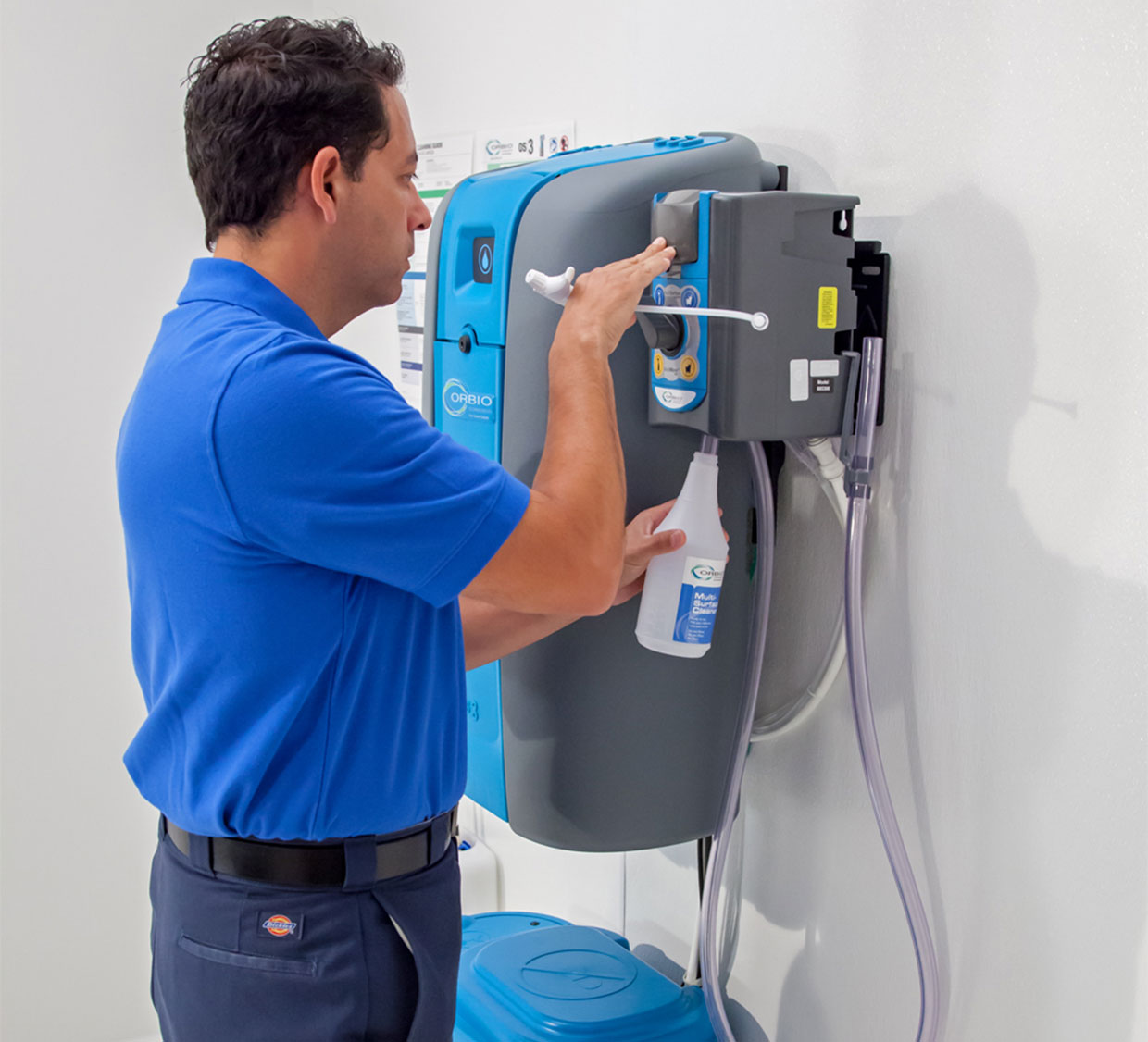A worker fills a spray bottle with cleaning solution generated on site by the Orbio os3 system.