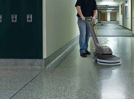 A custodian using the BR-1600-NDC Burnisher in a school.