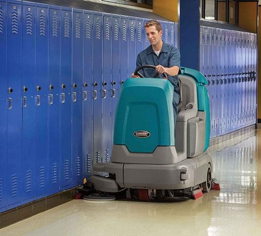 Tennant scrubber machine cleaning school floors
