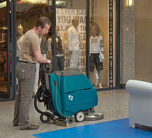 T2 Battery Walk-Behind Scrubber being used in a mall.