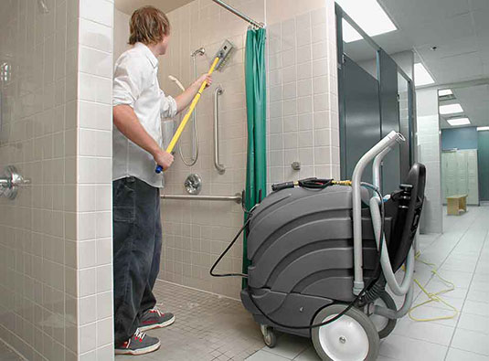 An employee cleaning a shower with the ASC-15 All-Surface Cleaner