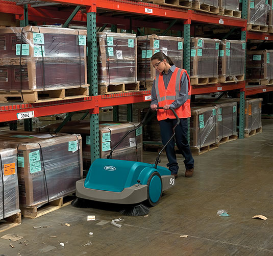 S3 Manual Sweeper being used in a warehouse.
