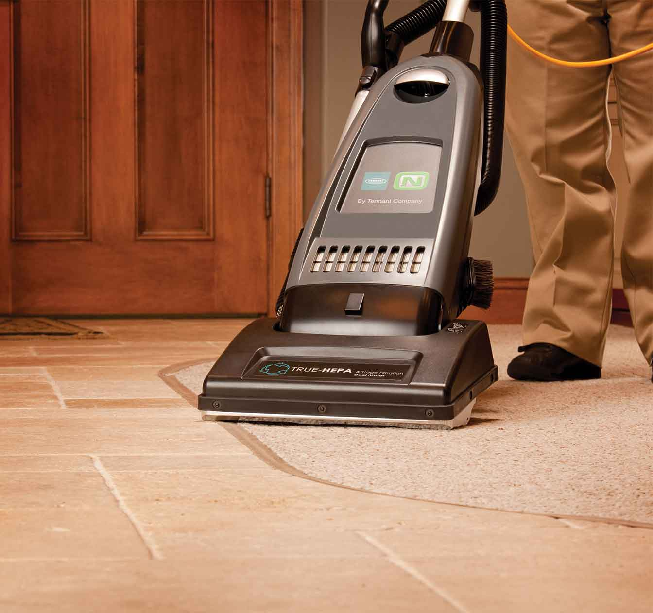 The V-DMU-14 Dual Motor Upright Vacuum cleaning two different surfaces.