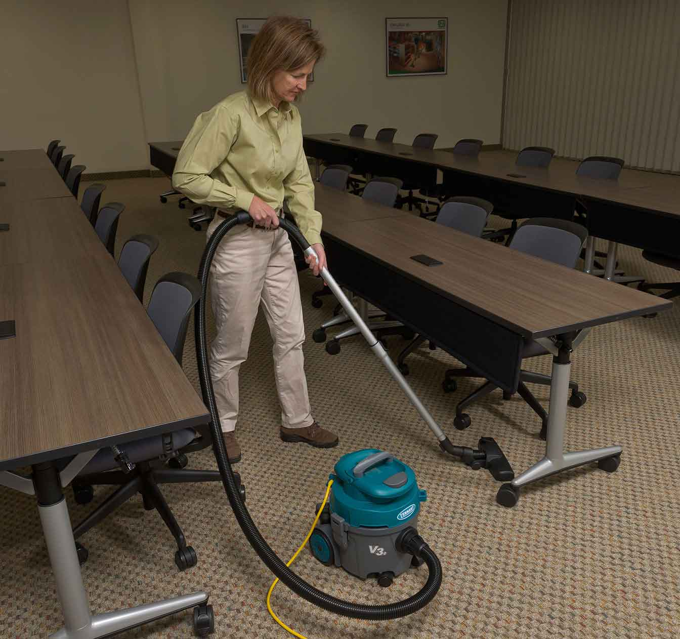 V3e Canister Vacuum cleaning a conference room floor.