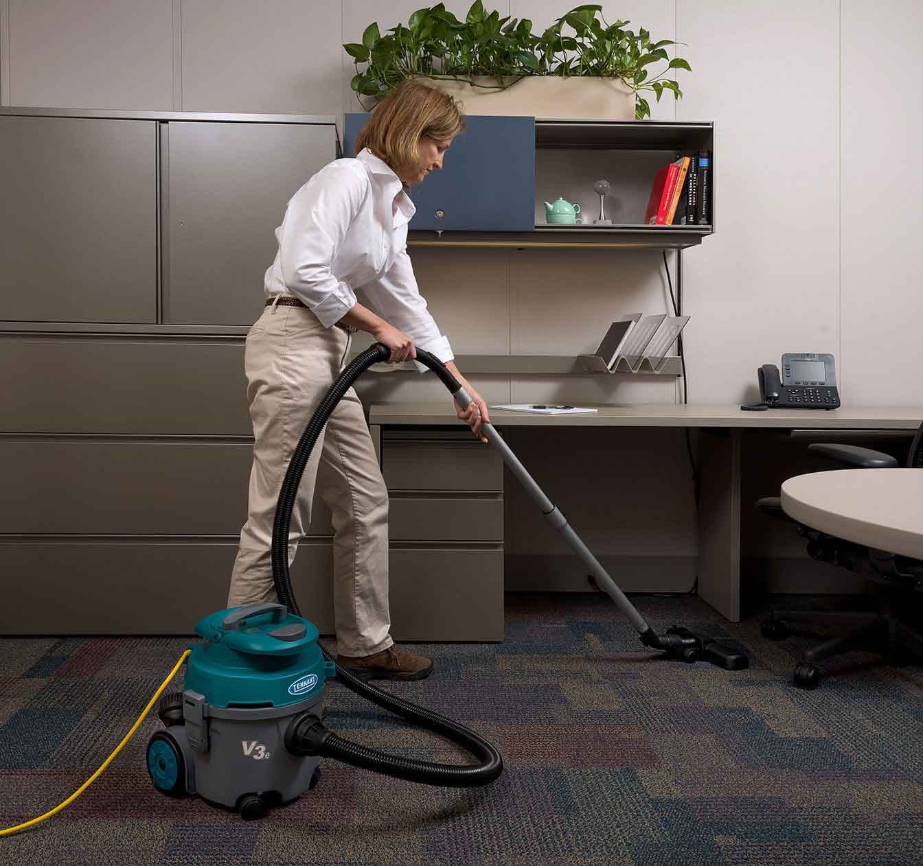 V3e Canister Vacuum vacuuming an office.