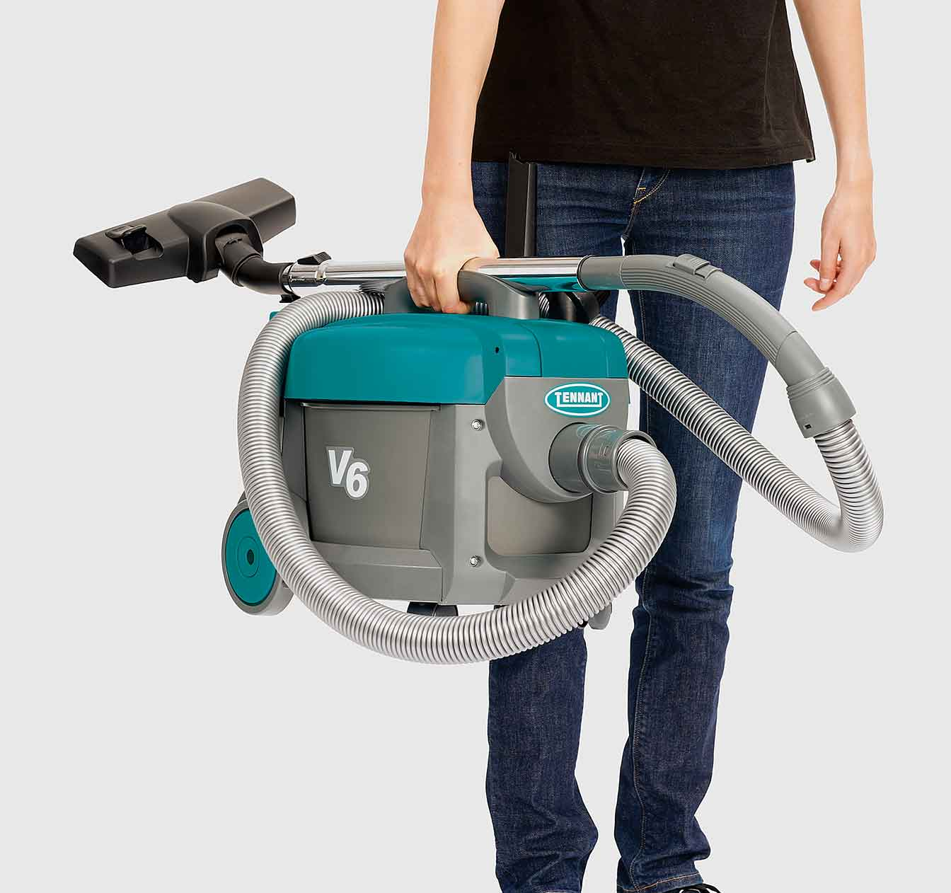 An employee carrying the V6 Dry Canister Vacuum.