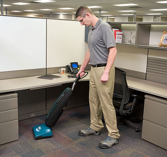 Custodian cleaning an office with the V-LWU-13B Lightweight upright vacuum