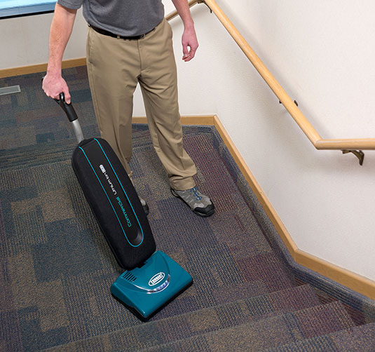 A custodian using a V-LWU-13B on carpeted stairs.